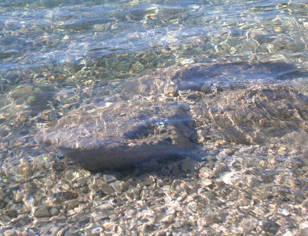 Ein großer Stein ist im klaren Wasser zu sehen.