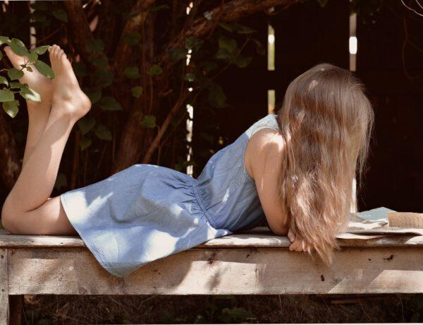 Mädchen liest entspannt ein Buch.