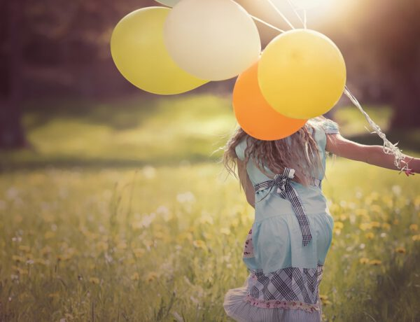 Mädchen rennt mit Luftballons über eine Wiese